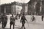 Květen 1945. Sovětští vojáci pochodují po Horním náměstí v Olomouci u poničené radnice. Orloj poškodily události války, byl přebudován v letech 1947-1955.