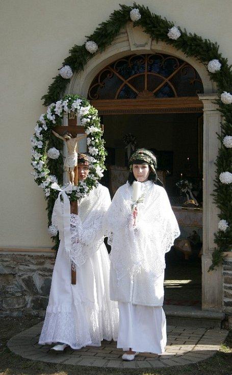 Matičky z kaple vynášejí nazdobený kříž.
