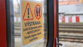 Cestující na to signalizaci upozorňuje i plakátek nalepený na skle dveří některých starších vlakových souprav.