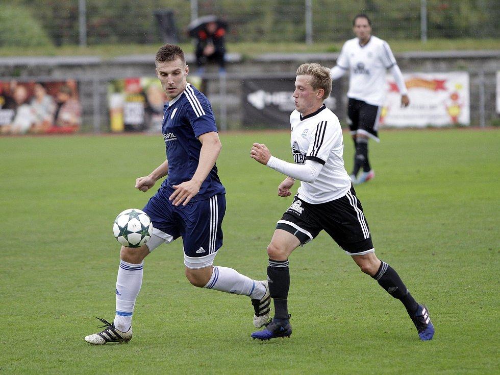 Fotbalisté Uničova remizovali s Rýmařovem (v bílém) 1:1. Petr Rajnoha, vlevo