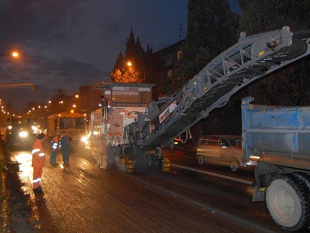Silničáři frézují asfaltový povrch vozovky i v noci.