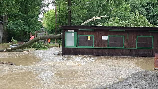 Přívalový déšť v pondělí rozvodnil potok Loučka, který pak zaplavil fotbalový areál v Haňovicích. Spadený strom poškodil kiosek, kde se prodává občerstvení.