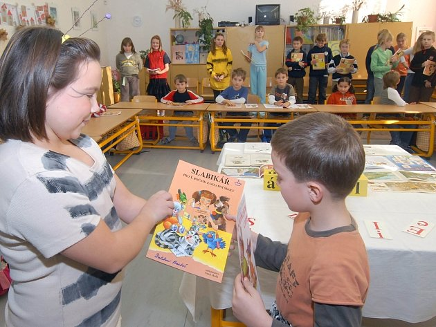 Páťáci předávali knihy malým spolužákům.