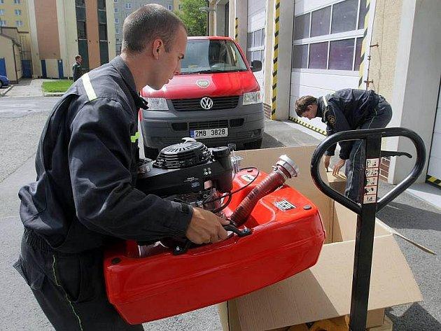 Hasiči nakládají čerpadla, které Olomoucký kraj posílá jako pomoc do povodněmi postižených severních Čech