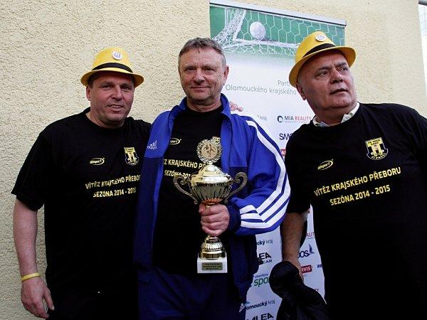 Fotbalisté Nových Sadů (ve žlutém) porazili Dolany 8:1 a radovali se zvítězství vsoutěži.  trenér Karel Trnečka spohárem