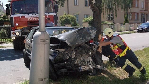 Hasiči se snaží odklidit nabouraný vůz.