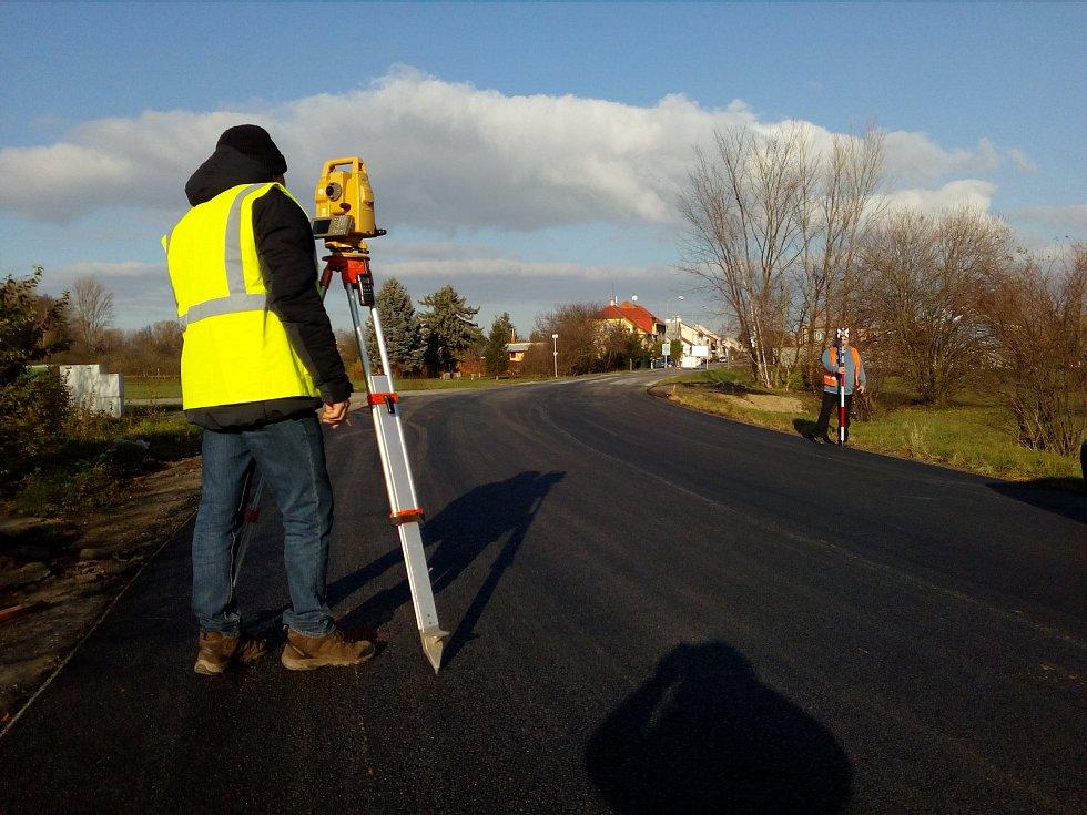 Geodeti zaměřují opravenou silnici mezi olomouckými Lazcemi a Chomoutovem. Už jen vzít bílou a namalovat vodorovné značení a je hotovo. Stříhání pásky na dokončené stavbě je naplánováno na středu 21.prosince. Původní termín byl 7.prosince.