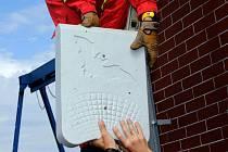 Profesionální hasiči HZS Olomouc pomocí lezecké techniky připevňují budku pro netopýry na jezu obtokového kanálu.