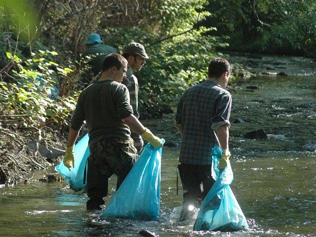 Brigádníci táhnou pytle s odpadky v proudu říčky Bystřice.