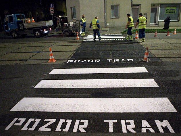 Pracovníci technických služeb vyznačují ve středu v noci v Hodolanské ulici přechod