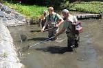 Rybáři zachraňují rybí osádku z téměř vyschlého Trusovického potoka.