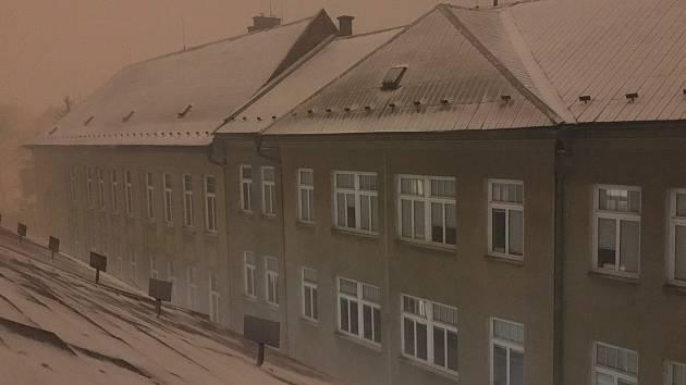 Před 19.hodinou se zvedl vítr a Olomouc se ponořila do bílé tmy. Teplota klesla z jednoho nad nulou na dva stupně pod bodem mrazu během pár minut. Na snímku vítr víří sníh na střechách domů v centru Olomouce.