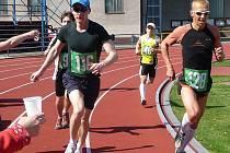 Vabroušek (č. 128) probíhá kolem občerstvovací stanice na atletickém stadionu
