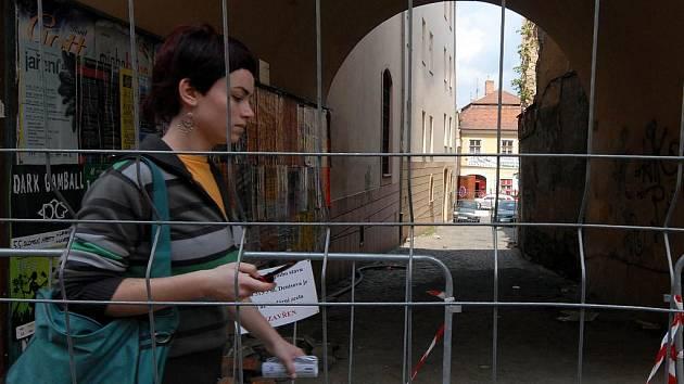 Kvůli havarijnímu stavu domu (na snímku část domu a zeď vpravo) museli stavebníci uzavřít průchod do Vodární ulice.