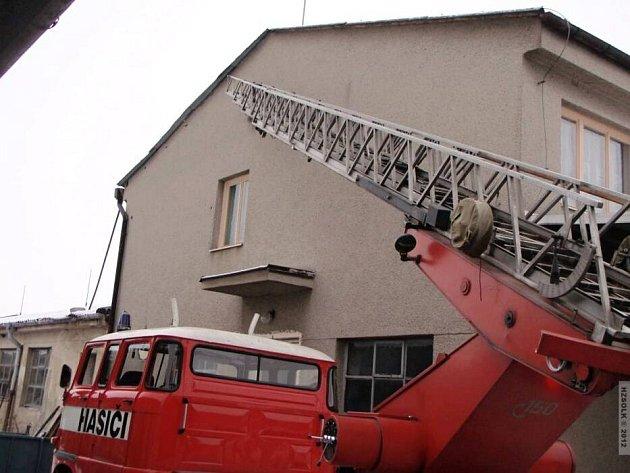 Hasiči zasahují u budovy, na jejíž střechu vylezl muž a chtěl skočit dolů
