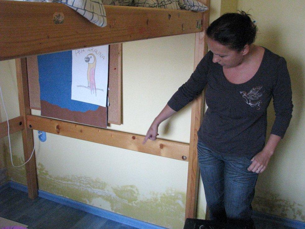 Kateřina Kolomazníková ukazuje vlhkou zeď a na ní plíseň.