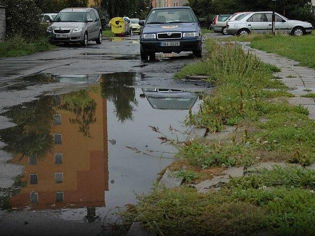 Chodníky v Mišákově ulici v Olomouci zarůstá tráva, dlaždice se drolí. Silnice je zase plná děr a po dešti kaluží.