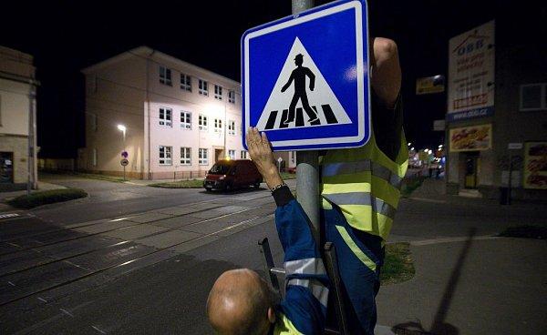 Pracovníci technických služeb vyznačují ve středu vnoci vHodolanské ulici přechod