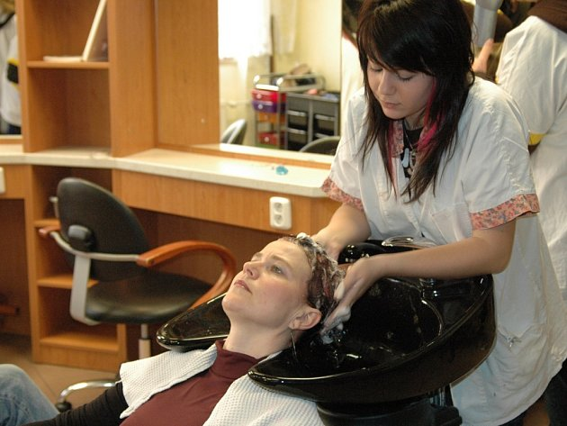 Studentka myje hlavu zákaznici.