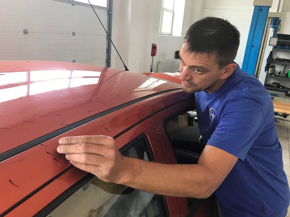 Na opravy karoserií poškozených krupobitím nasadily firmy do Olomouce posily. Motoristům pomáhá například Doktor Důlek a jeho mezinárodní tým. Využívá několik technologických postupů. Na snímku lepící metoda.