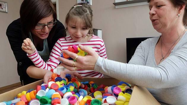 Víčka od stovek plastových lahví dostala ve středu odpoledne od redakce Olomouckého deníku rodina postižené Simonky Sliwkové z Olomouce (uprostřed)