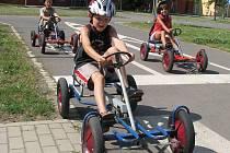 Děti právě projíždějí křižovatkou na dopravním hřišti