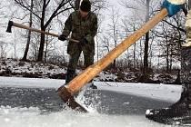 Rybáři prosekávají díry do ledu na rybníku v Černovíře