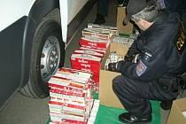 Celníci přepočítávají nezdaněné cigarety, které zabavili při jedné z kontrol.