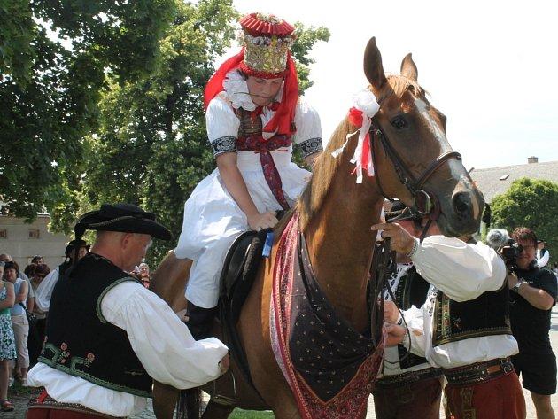 Muži pomáhají králi usednout v dívčím kroji na koně