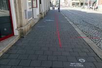 Červená čára upozorňující na zúžení chodníků při projektované rekonstrukci ulice 8. května v Olomouci
