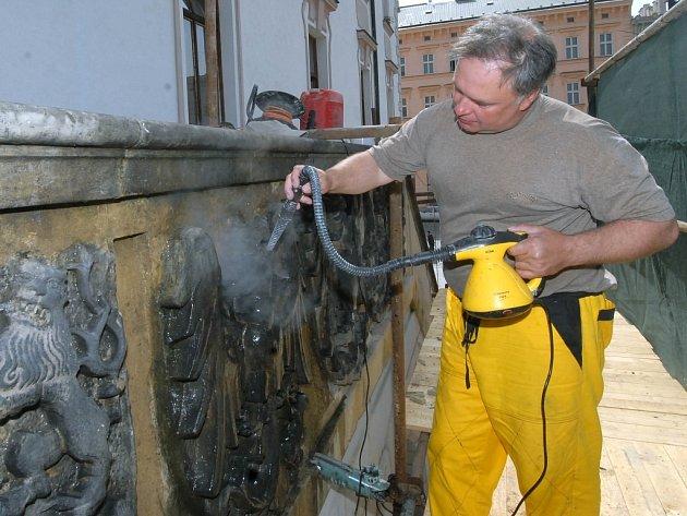 Sochař Karel Hořínek čistí vodní párou pískovec na schodišti olomoucké radnice.