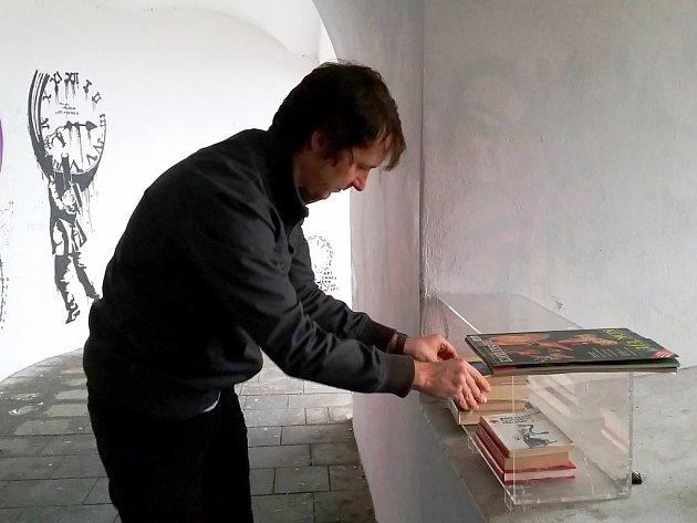 Spoluautor projektu olomouckých miniknihoven Radim Schubert opravuje poničený plexisklový box na knihy v Lomené galerii