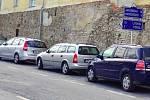 V Bouzově se obec snaží dostat motorizované návštěvníky na centrální parkoviště. Z parkovného má ročně půl milionu korun. Na snímku turisty zaplněné parkoviště na obecní povolenku.