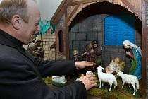 Kněz Eduard Krumpolc připravuje betlém v hněvotínském kostele