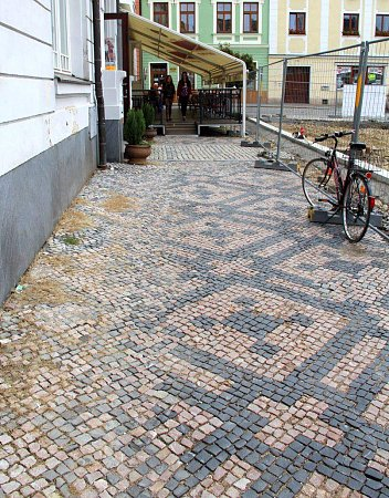 Chodníky na rekonstruovaném náměstí vLitovli se vrátí do své původní podoby a tvořit by je měly obrazce. Zbytky jsou ještě kvidění uHotelu Záložna.