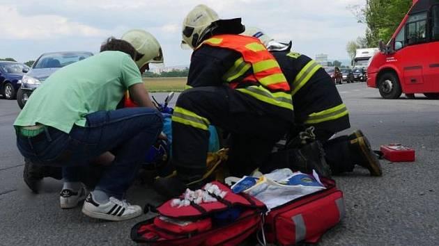 Hasiči a záchranáři pomáhají zraněné řidičce skútru po srážce s náklaďákem v ulici Šlechtitelů