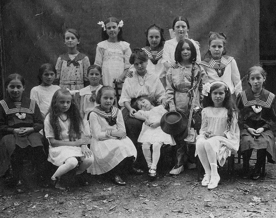 """Historický snímek z roku 1912 zachycující účastnice školního divadelního představení """"Dráteník"""" v obci Komárov. Zcela vpravo sedící je Hedvika Vondřichová, budoucí manželka dalšího Poldaufova syna, Antonína ml."""
