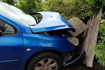Řidiče auta zastavil plot rodinného domu. Vozidlo hasiči vyprostí jeřábem