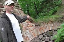 Kastelán Dalibor Urban ukazuje na bránu, která byla objevena při opravách zdiva za východní baštou hradu Litice.