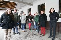 Skupina studentů si z podloubí hostince Krčma  prohlíží  travnatou plochu u křižovatky, kterou má oživit jeden ze sochařských počinů. Vpravo Zuzana Ambrožová, vedle ní Přemysl Kokeš.