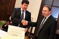 Jan Lustyk (vlevo), ředitel společnosti Rieter CZ, předává ústeckému starostovi Petru Hájkovi šek na více než půl milionu korun.