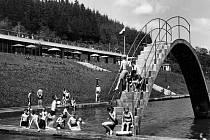 Známé koupaliště v Křivolíku, ještě s budovou starých dřevěných šaten, zachytil další snímek. Opět jsou vidět i početní vodymilovní návštěvníci.
