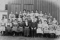 Josef B. Hubálek se svými žačkami u dřevěného leziště ve dvoře hasičské zbrojnice v Chorinově ulici po roce 1909.Čtvrtá zprava v dolní řadě je jeho dcera Božena.