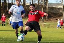Středopolař Jablonného Petr Čermák se natahuje po míči. Přibíhá lanškrounský Komínek.