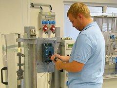 Pracovník vývojové zkušebny   připravuje kompaktní jistič  pro testy mechanické odolnosti.
