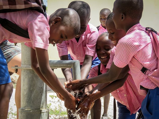 Školáci nabírají vodu ze znovuzprovozněné studny Marie Goretti.