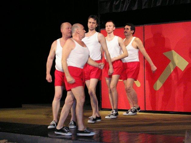 Divadelníci z Viceny před scénou s výraznými motivy srpu a kladiva.