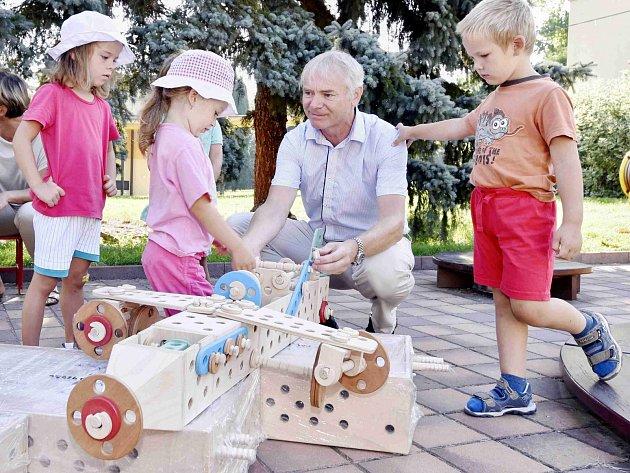 Generální ředitel Iveco Czech Republic Jiří Vaněk s dětmi nad stavebnicí.