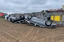 Náklaďák převážějící auta skončil i s nákladem na boku v poli