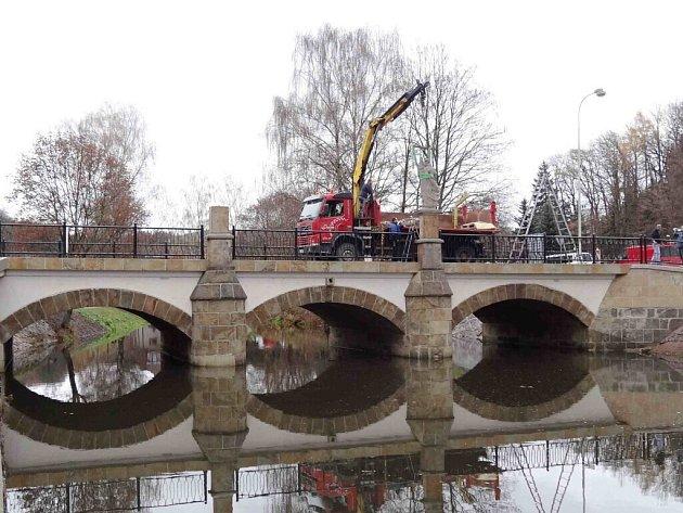 Z montáže soch, které se na most vrátily po renovaci.